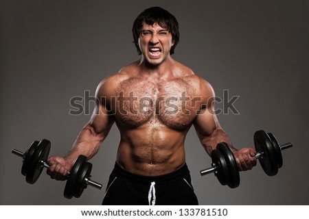 Muscular guy working out with dumbbells over grey background - stock photo