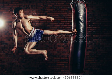 muscular handsome fighter giving a forceful forward kick during a practise round with a boxing bag, kickboxing. - stock photo