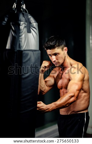 muscular handsome fighter man punch boxing bag