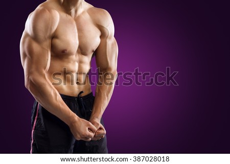 Muscular Handsome Fitness Man Demonstrates His Abdominal Muscles On Purple Background - stock photo