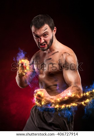 muscular handsome man fighter with fire arms - stock photo