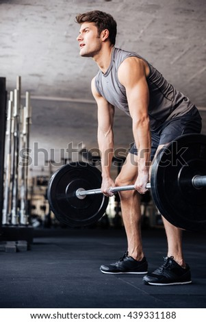 Muscular handsome man workout with barbell in fitness gym - stock photo