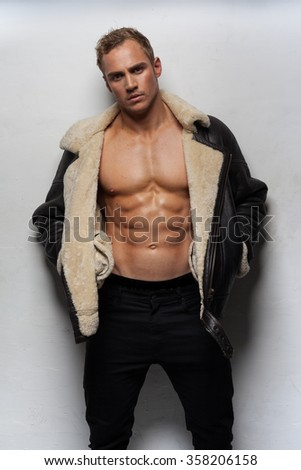 Muscular handsome sexy guy posing wearing jacket - stock photo