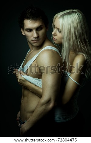 muscular handsome sexy guy with pretty woman, on dark background, glamour green light - stock photo