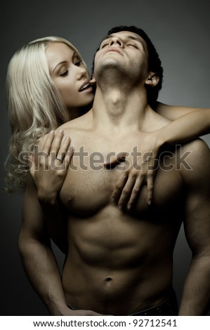 muscular handsome sexy guy with pretty woman, on dark background, glamour light