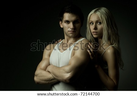 muscular handsome sexy guy with pretty woman on dark background, look on camera - stock photo