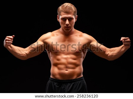 Muscular heavy sexy man in tense pose with raised arms and tense muscles, with naked torso, dressed in black shorts and shadow on the face. Isolated on black background - stock photo