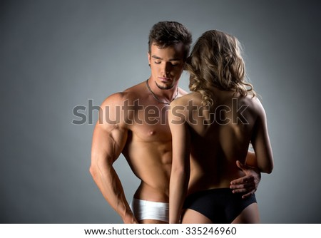 Muscular hunk embracing topless model by waist - stock photo