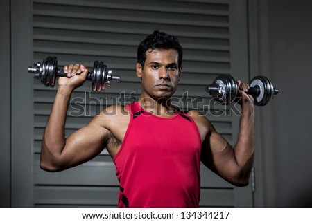 Muscular Indian man exercising with weight training equipment at a sports gym.