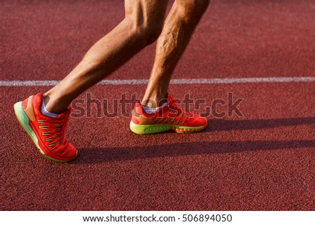 Muscular legs of man in sneakers on running track