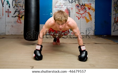 Muscular looking boxer doing press-ups in a graffiti clad suburban basement Focus on the dorsal muscles and biceps - stock photo
