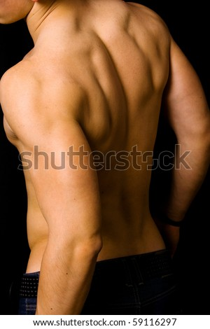 muscular male back on black background - stock photo