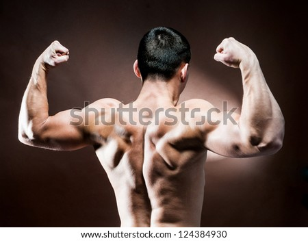 muscular male back on brown background - stock photo