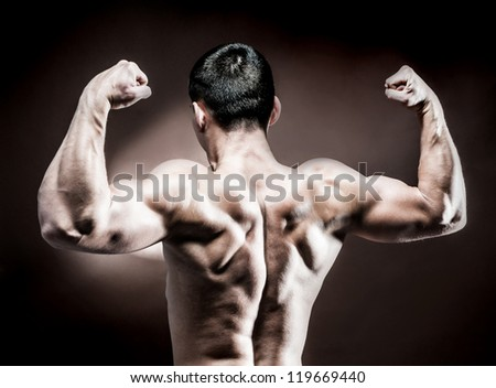 muscular male back on dark background - stock photo