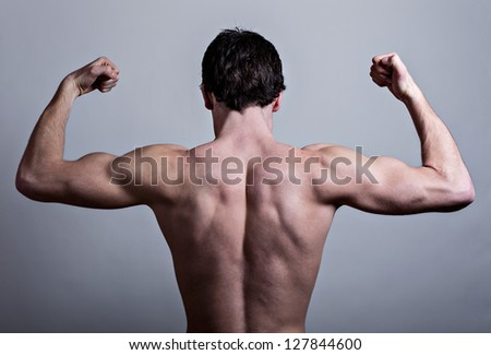 Muscular male back over gray background - stock photo