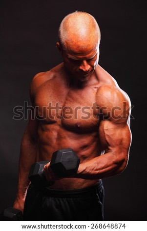 Muscular male bodybuilder flexing biceps with dumbbell - stock photo