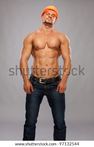 Muscular male builder on gray  background - stock photo