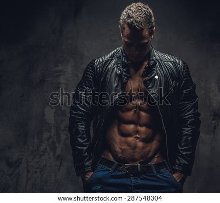Muscular male in blue jeans and black jacket wearing on shirtless body. Isolated on grey background. - stock photo
