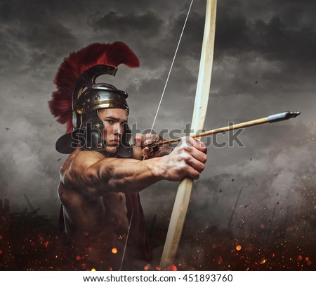 Muscular male in spartan costume shooting from wooden bow under stormy sky. - stock photo