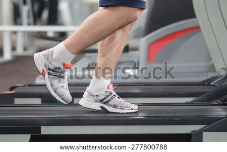 Muscular male legs on a treadmill at the gym. - stock photo