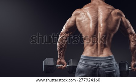Muscular male model bodybuilder doing exercises with dumbbells, turned back. Isolated over black background. Photo with copy space - stock photo