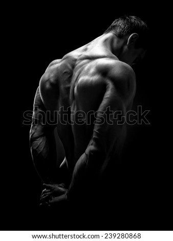 Muscular male model bodybuilder preparing for fitness training, turned back. Studio shot on black background. Black and white photo. - stock photo