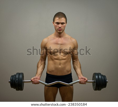 Muscular male model doing exercises with barbell. - stock photo