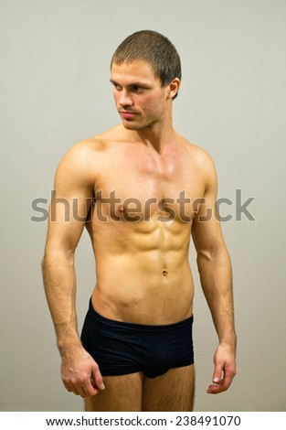 Muscular male model posing on grey background. - stock photo