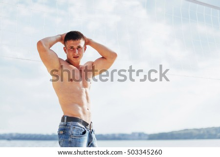 muscular male model with perfect body posing in blue jeans on sand