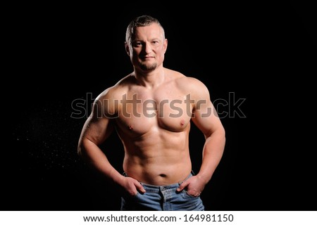 Muscular male posing on black background