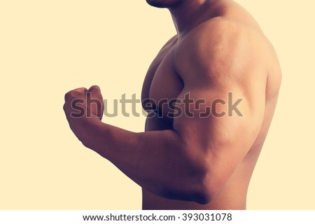 Muscular male showing big arm muscles.grunge vintage style. - stock photo