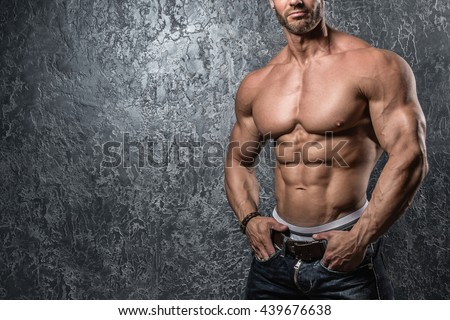 Muscular male torso against concrete wall - stock photo