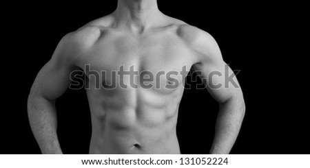 Muscular male torso in Black and white shot in studio against a black background. - stock photo