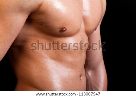 Muscular male torso on black background