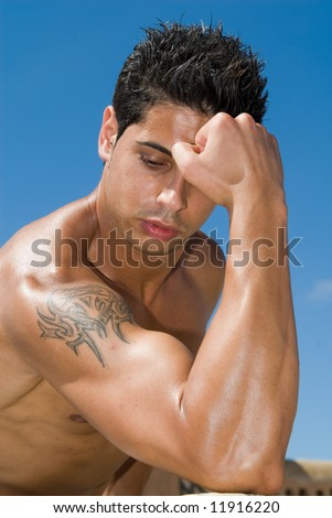 Muscular male torso on the blue sky