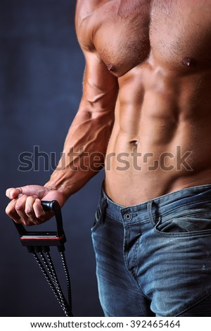 Muscular male torso with the chest expander - stock photo
