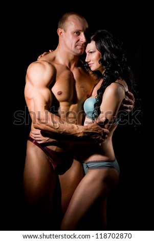 Muscular man and a woman on a dark background - stock photo