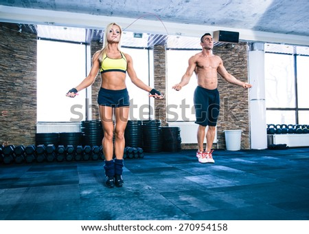 Muscular man and beautiful sporty woman workout with jumping rope in crossfit gym - stock photo