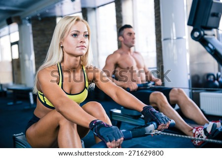 Muscular man and sporty woman workout on training simulator in crossfit gym - stock photo