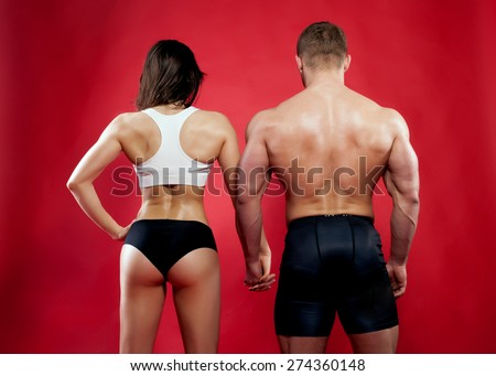 Muscular man and woman posing over red background. Back view. - stock photo