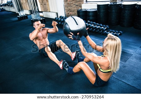 Muscular man and woman workout with fitball at gym - stock photo