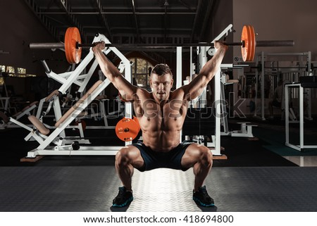 Muscular man at a crossfit gym lifting a barbell. - stock photo
