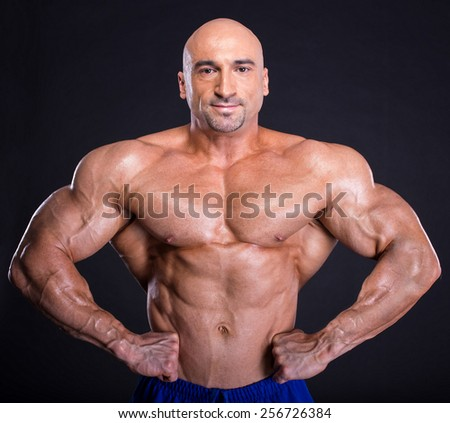 Muscular man bodybuilder is demonstrating his perfect muscular body  muscles and arms. Isolated over dark background. - stock photo