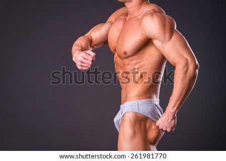 Muscular man bodybuilder. Man posing on a black background, shows his muscles. - stock photo