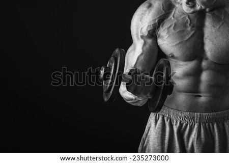Muscular man bodybuilder . Man posing on a black background, shows his muscles. Bodybuilding, posing, black background, muscles. - stock photo