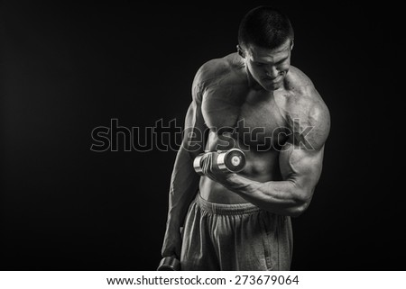Muscular man bodybuilder. Man posing on a black background, shows his muscles. Bodybuilding, posing, black background, muscles