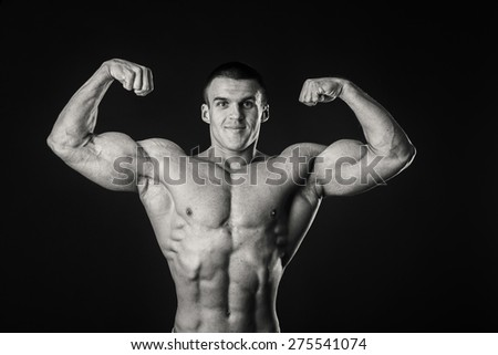Muscular man bodybuilder. Man posing on a black background, shows his muscles. Bodybuilding, posing, black background, muscles - the concept of bodybuilding. Article about bodybuilding. - stock photo