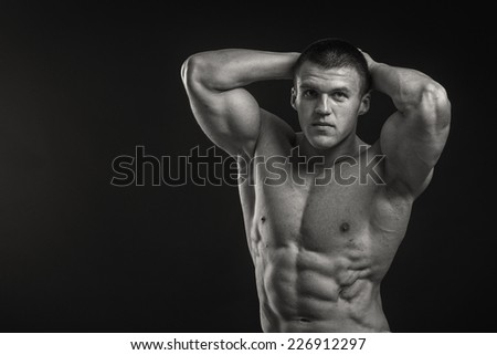 Muscular man bodybuilder with tattoos. Man posing on a black background, shows his muscles. Bodybuilding, posing, black background, muscles.