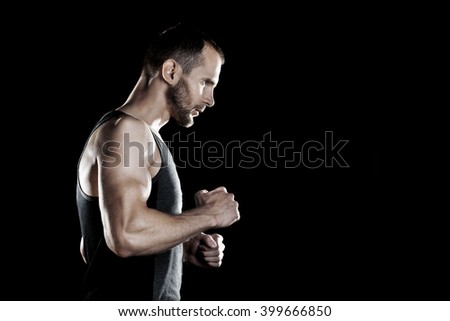 muscular man,  clasps hands in  fist, black background, place for text on the right - stock photo