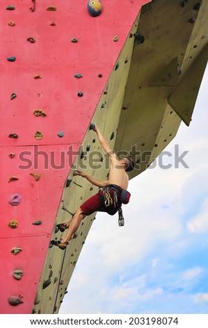 Muscular man climbing on a big wall - stock photo
